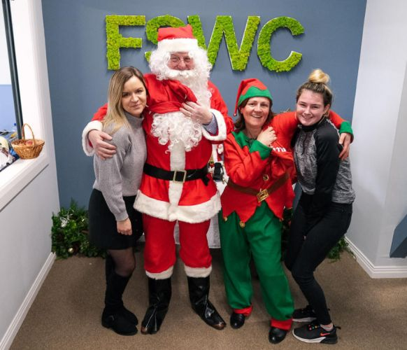 Santa at FSWC sign with Creche staff